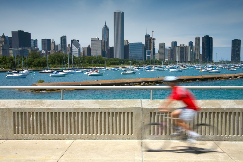 Man on a bicycle whizzes by with the Chicago skyline in background
